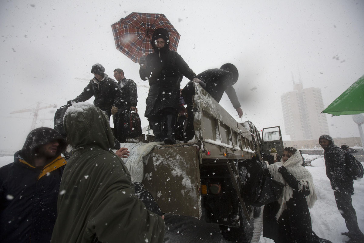 Israeli soldiers help stranded passengers off of an army truck to a temporary shelter after they had to leave their vehicles because of heavy snowfall in Jerusalem