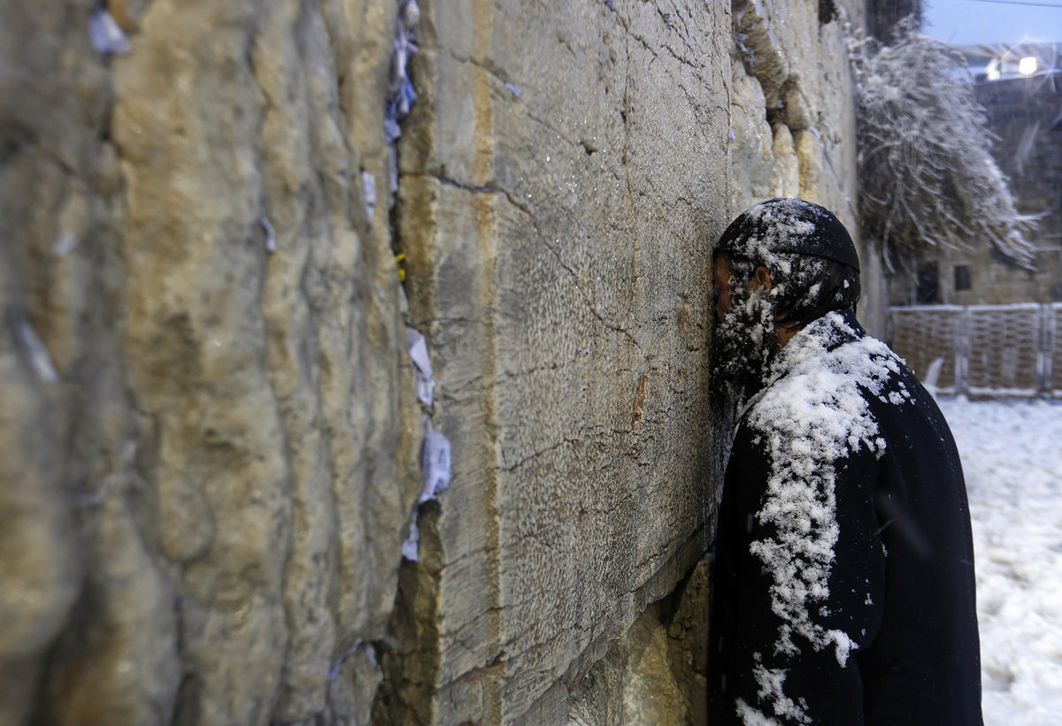 An Ultra-Orthodox Jewish man prays at  the Western Wall in Jerusalem's Old City during a snowstorm