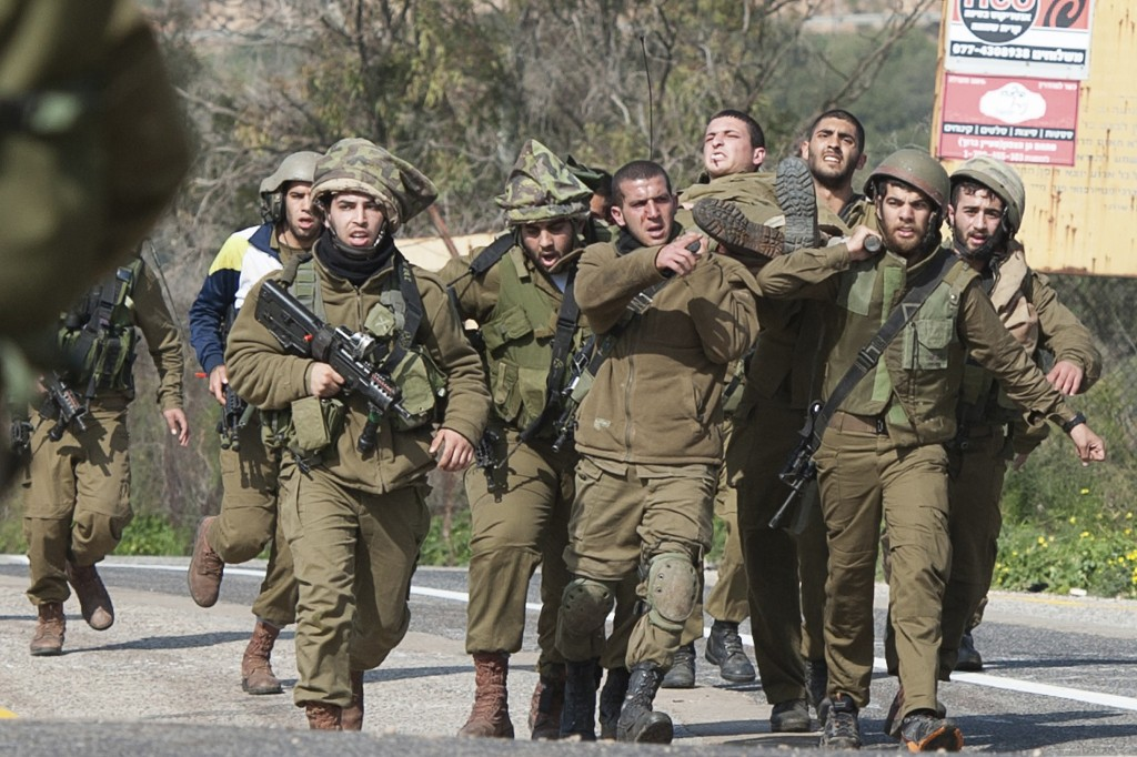 Israeli soldiers carry a wounded comrade on a stretcher near Israel's border with Lebanon